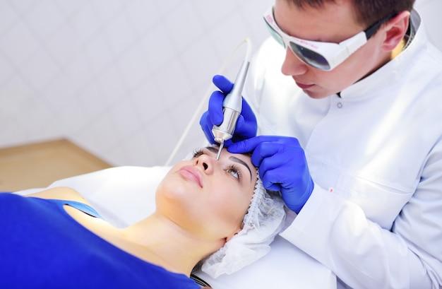 Kosmetyczka Chirurg Usuwa Pigmenty I Siatki Naczyniowe Na Skórze Pacjenta Premium Zdjęcia