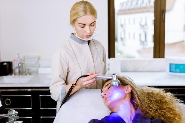 Kosmetyczka Lekarz Robi Niebieską Diodę Do Terapii światłem Klientowi W Salonie Piękności, Fototerapia Twarzy Do Oczyszczania Porów Skóry. Zabiegi Przeciwstarzeniowe I Procedura Odmładzania Zdjęć, Zbliżenie Premium Zdjęcia