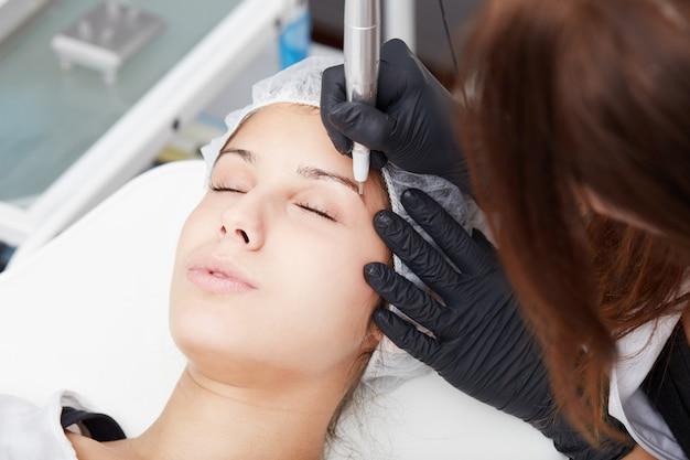Kosmetyczka nakłada makijaż permanentny na brwi Premium Zdjęcia