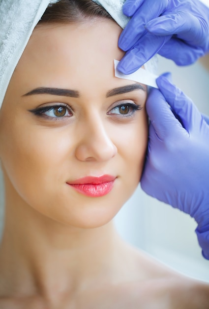 Kosmetyczka woskowanie brwi młodej kobiety w centrum spa Premium Zdjęcia