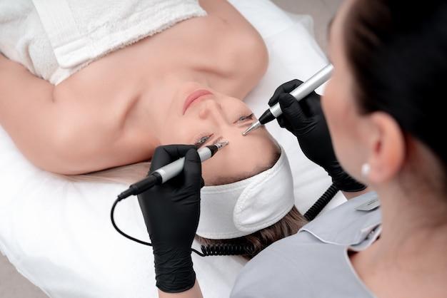 Kosmetyka. Piękna Kobieta W Klinice Spa Otrzymujących Stymulujące Elektryczne Leczenie Twarzy Od Terapeuty. Zbliżenie Młodej Twarzy Kobiety Podczas Terapii Mikroprądowej Premium Zdjęcia