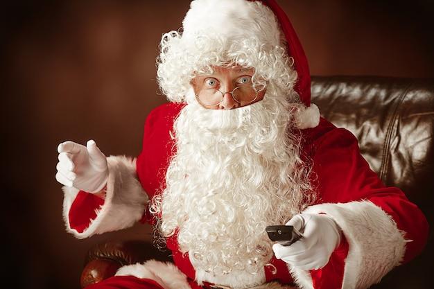 Kostium świętego Mikołaja Z Luksusową Białą Brodą, Czapką świętego Mikołaja I Czerwonym Kostiumem Na Czerwonym Tle Studio Darmowe Zdjęcia