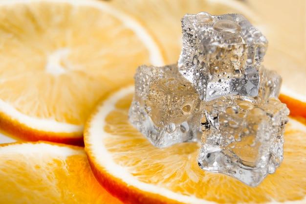 Kostka Lodu Na Pomarańczowym Tle. świeże Pomarańcze Premium Zdjęcia