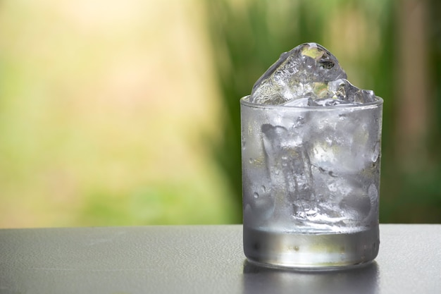 Kostka lodu w szkle na stole z natury tłem Premium Zdjęcia