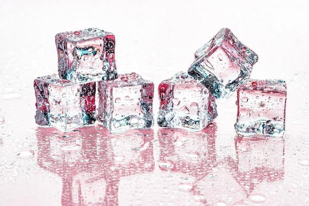 Kostki lodu na różowym tle Premium Zdjęcia