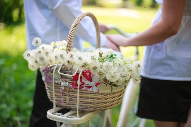 Kosz z mleczami i kwiatami na rowerze romantyczny spacer faceta i dziewczyny na świeżym powietrzu z rowerem. Premium Zdjęcia