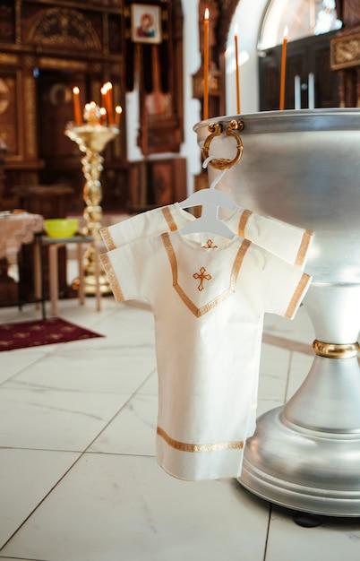 Koszula Do Chrztu Wisi Na Wieszaku Na łaźni W Kościele. Chrzest Dziecka. Premium Zdjęcia