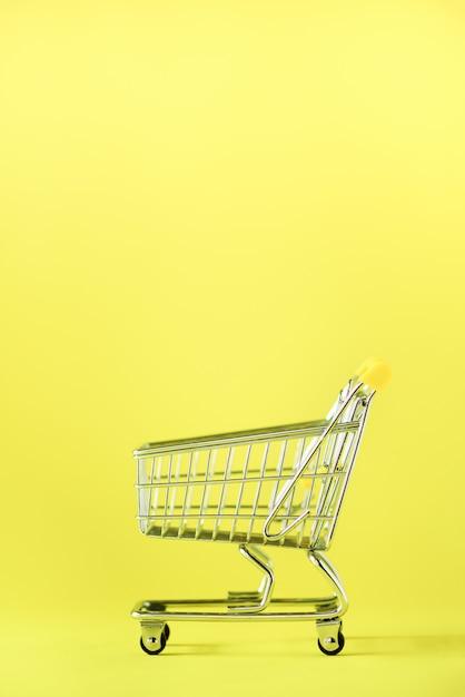 Koszyk na żółtym tle. wózek sklepowy w supermarkecie. sprzedaż, rabat, koncepcja shopaholism. trend społeczeństwa konsumpcyjnego Premium Zdjęcia