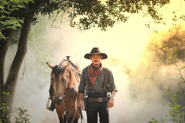 Kowboj i koń w lesie Premium Zdjęcia