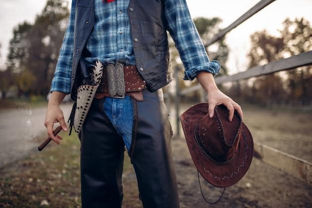 Kowboj W Skórzanych Ubraniach Pozuje Z Cygarem W Zagrodzie Dla Koni Premium Zdjęcia