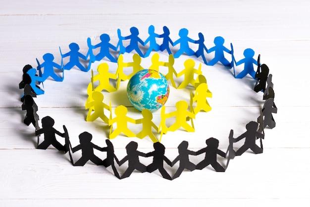 Krąg ludzi papieru, trzymając się za ręce na całym świecie, wykonane z wyciętego papieru Premium Zdjęcia