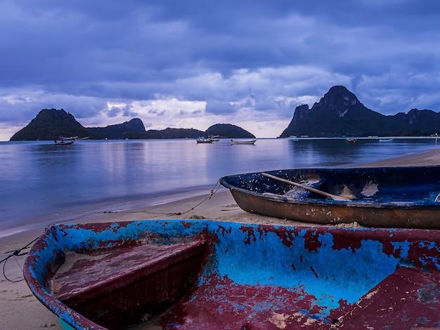 Krajobraz morze i mała łódka w mrocznym czasie, tajlandia Premium Zdjęcia