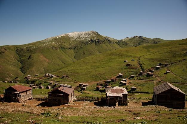 Krajobraz wzgórz pokrytych zieloną trawą i domy w tle jasnego nieba Premium Zdjęcia