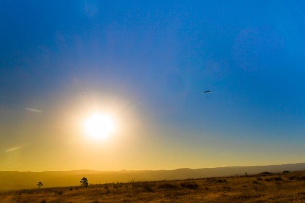 Krajobraz zaćmienia w górach i paralotniarstwa na niebie Premium Zdjęcia