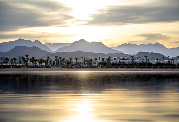 Krajobrazowe Niebo Odbija Się W Morzu W Zachodzącym świetle. Wybrzeże Miasta Z Górami Na Horyzoncie. Darmowe Zdjęcia