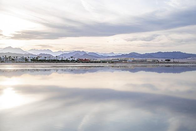 Krajobrazowe Niebo Odbija Się W Morzu. Wybrzeże Miasta Z Górami Na Horyzoncie. Darmowe Zdjęcia