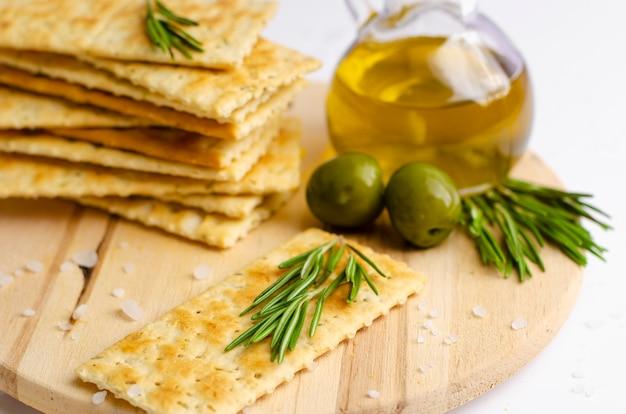 Krakersy bezglutenowe z rozmarynem, oliwkami i oliwą z oliwek na desce. Premium Zdjęcia