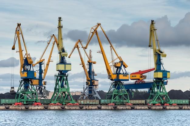 Krany wiosłują wzdłuż linii brzegowej portu Premium Zdjęcia