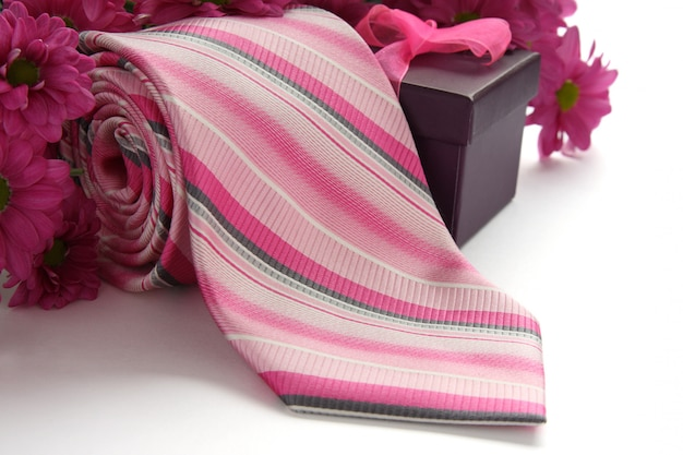 Krawat i pudełko z kwiatami na białym Premium Zdjęcia