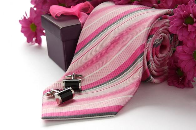 Krawat i spinki do mankietów z kwiatami nad białymi Premium Zdjęcia