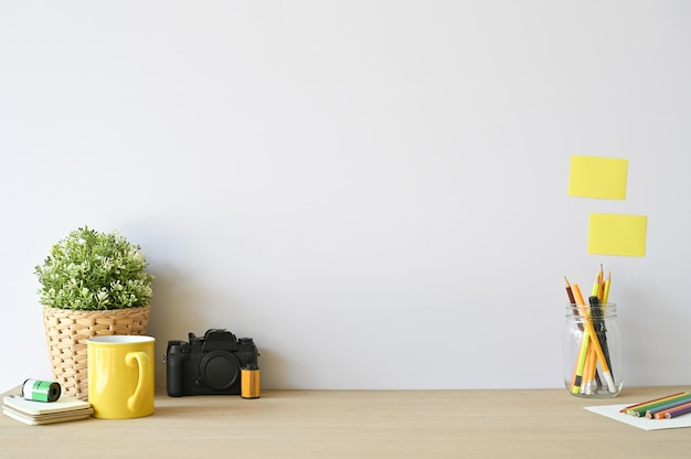 Kreatywna kamera robocza i materiały biurowe na drewniane biurko z miejsca na kopię. Premium Zdjęcia