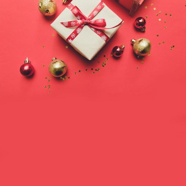 Kreatywna kompozycja z czerwonym pudełkiem, wstążkami, dużymi i małymi kulkami z czerwonego złota, świątecznymi dekoracjami na czerwono. Premium Zdjęcia