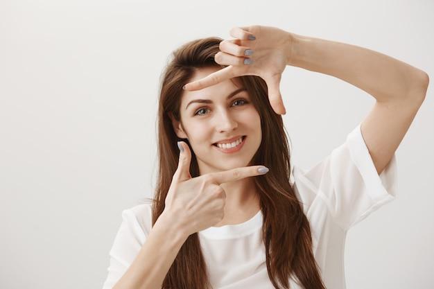 Kreatywna Młoda Kobieta Robi Gest Przechwytywania, Wyobrażając Sobie Scenę I Uśmiecha Się Zadowolony Darmowe Zdjęcia