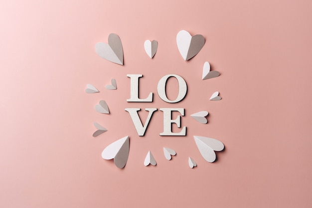 Kreatywne, Płaskie Ukształtowanie Słowa Miłość Na Miękkiej ścianie Z Papierowymi Sercami. Premium Zdjęcia