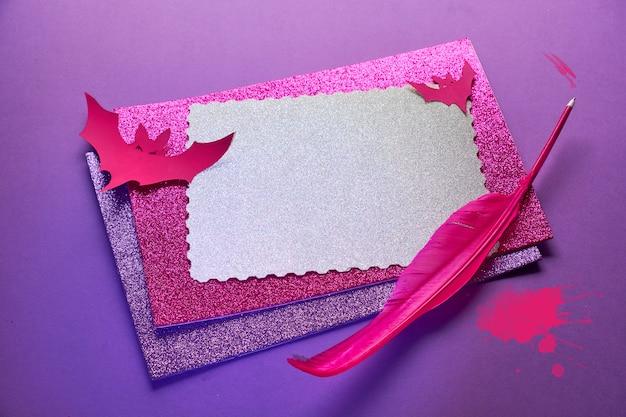 Kreatywne Tło Halloween W świecącym Neonowym Różu I Fioletu Ze Stosem Błyszczącego Papieru, Pióro I Papierowe Nietoperze Miejsce Na Tekst Na Górnej Karcie. Premium Zdjęcia