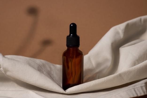 Kreatywne Zdjęcie Butelki Kosmetycznej Z Pipetą Na Beżowym Materiale I Brązowym Tle Z Cieniem Tropikalnego Kwiatu. Widok Z Boku Reklamy Premium Zdjęcia