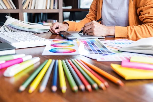 Kreatywny grafik pracujący na doborze kolorów i rysowaniu na tablecie graficznym Premium Zdjęcia