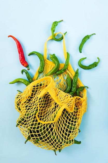 Kreatywny układ zielone papryczki chilli. zielone warzywa w żółtej sznurkowej torbie. kupa zielonej papryki o nazwie frigitelli Premium Zdjęcia