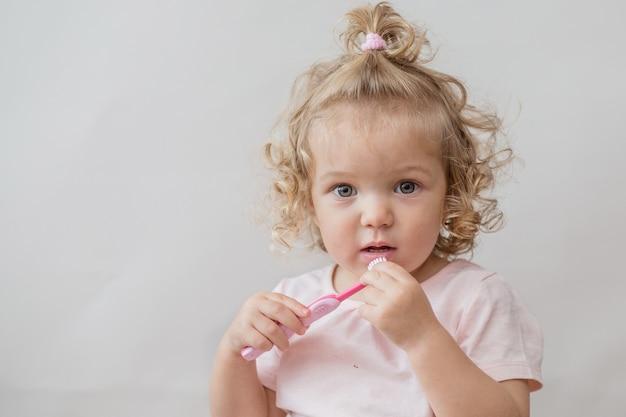 Kręcone Piękna Dziewczynka Ze Szczoteczką Do Zębów Na Szarej ścianie Premium Zdjęcia