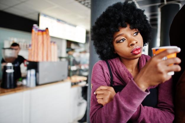 Kręcone Włosy African American Kobieta Nosić Na Sweter Postawiony W Kawiarni Kryty Z Filiżanką Herbaty Lub Kawy. Premium Zdjęcia