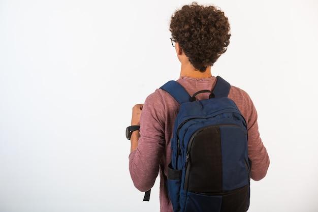 Kręcone Włosy Chłopiec W Okularach Optique, Trzymając Plecak. Darmowe Zdjęcia