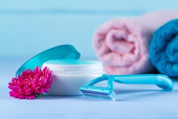Krem, brzytwa dla kobiet, ręczniki i różowy kwiat. epilacyjny. usuwanie niechcianych włosów. Premium Zdjęcia