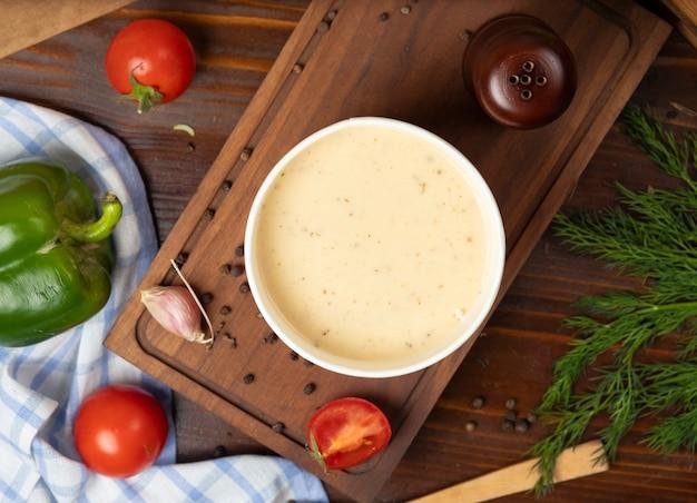 Kremowa zupa grzybowa w misce jednorazowego użytku z zielonymi warzywami. Darmowe Zdjęcia