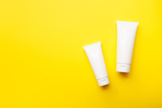 Kremowe Butelki Na Jasnym żółtym Tle, Widok Z Góry, Miejsce. Koncepcja Produktów Kosmetycznych I Pielęgnacji Skóry. Makieta. Premium Zdjęcia