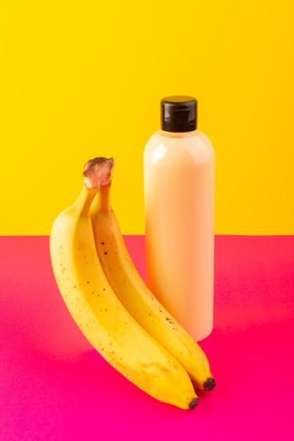 Kremowy Szampon Z Plastikowej Butelki Z Widokiem Z Przodu Z Czarną Nakrętką Izolowaną Wraz Z Bananami Na Różowo-żółtym Tle Kosmetyki Pielęgnacja Włosów Darmowe Zdjęcia
