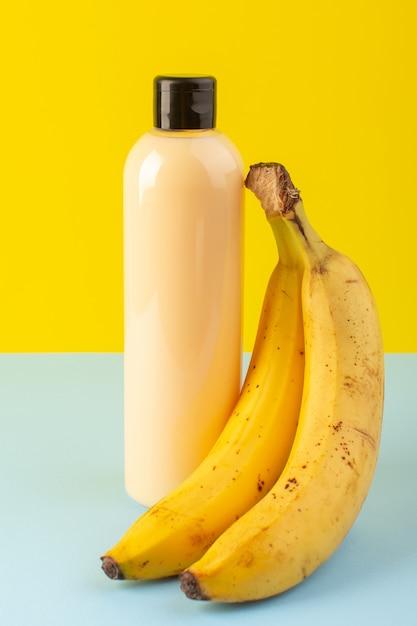 Kremowy Szampon Z Plastikowej Butelki Z Widokiem Z Przodu Z Czarną Nakrętką Izolowaną Wraz Z Bananami Na żółto-lodowo-niebieskim Tle Kosmetyki Pielęgnacja Włosów Darmowe Zdjęcia