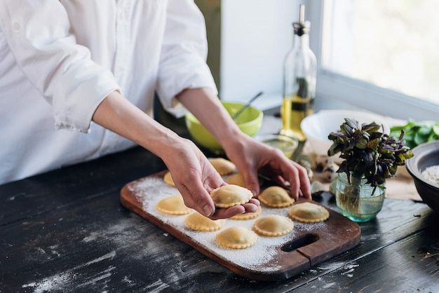 Krok Po Kroku Szef Kuchni Przygotowuje Ravioli Z Serem Ricotta, żółtkami Przepiórczymi I Szpinakiem Z Przyprawami. Szef Kuchni Przygotowuje Się Do Ravioli Premium Zdjęcia