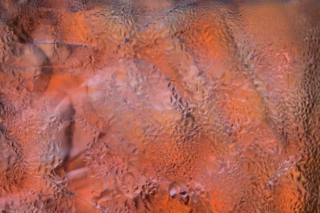Kropelki wody na szybie z kolorowym tłem Premium Zdjęcia