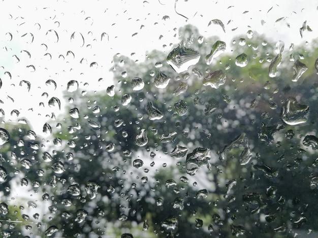 Kropla deszczu spadająca na szybę samochodu. Premium Zdjęcia