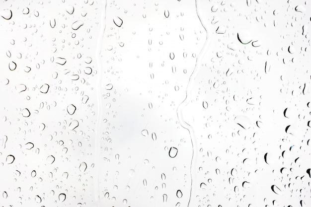Krople deszczu na szkle. sylwetki kropli wody na przezroczystej powierzchni. Premium Zdjęcia