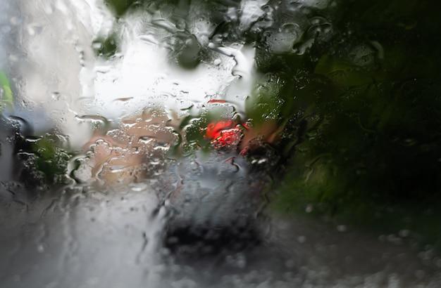 Krople Deszczu Na Szybie Przedniej Z Niewyraźnymi Nocnymi światłami Miasta W Tle. Premium Zdjęcia