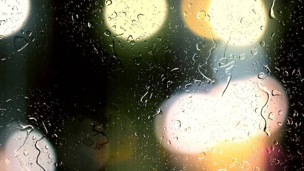 Krople Deszczu Spływają Po Szybie Na Tle Bokeh Poruszających Się Samochodów Premium Zdjęcia