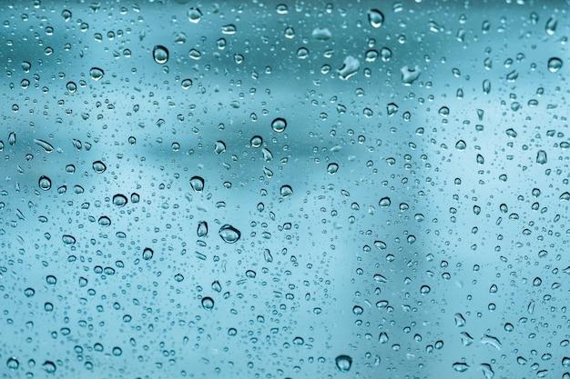 Krople deszczu, woda spada na szkło wiosną. abstrakcyjne tło Premium Zdjęcia