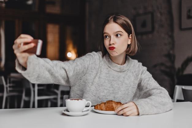 Krótkowłosa Kobieta W Kaszmirowej Bluzie Zamówiła W Kawiarni Rogalika I Cappuccino I Robi Selfie. Darmowe Zdjęcia