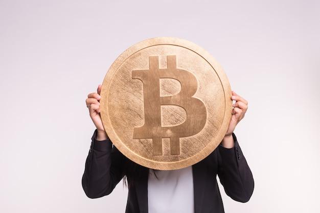 Kryptowaluta, Pieniądze Internetowe I Koncepcja Blockchain. Duży Bitcoin W Ręce Kobiety Na Białym Tle Premium Zdjęcia
