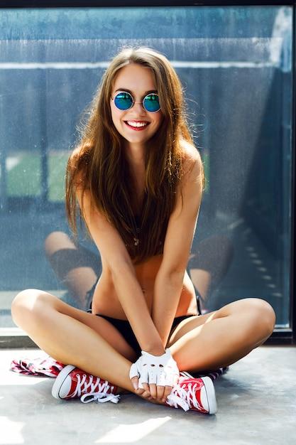 Kryty Jasny Letni Portret Modnej Stylowej Szczęśliwej Hipster Kobiety, Palący I Dobrze Się Bawiący, Ma Długie Brunetki, Idealnie Opalony, Dopasowany Do Szczupłego Ciała, Ubrany W Krótki Top I Okrągłe Okulary Przeciwsłoneczne. Darmowe Zdjęcia